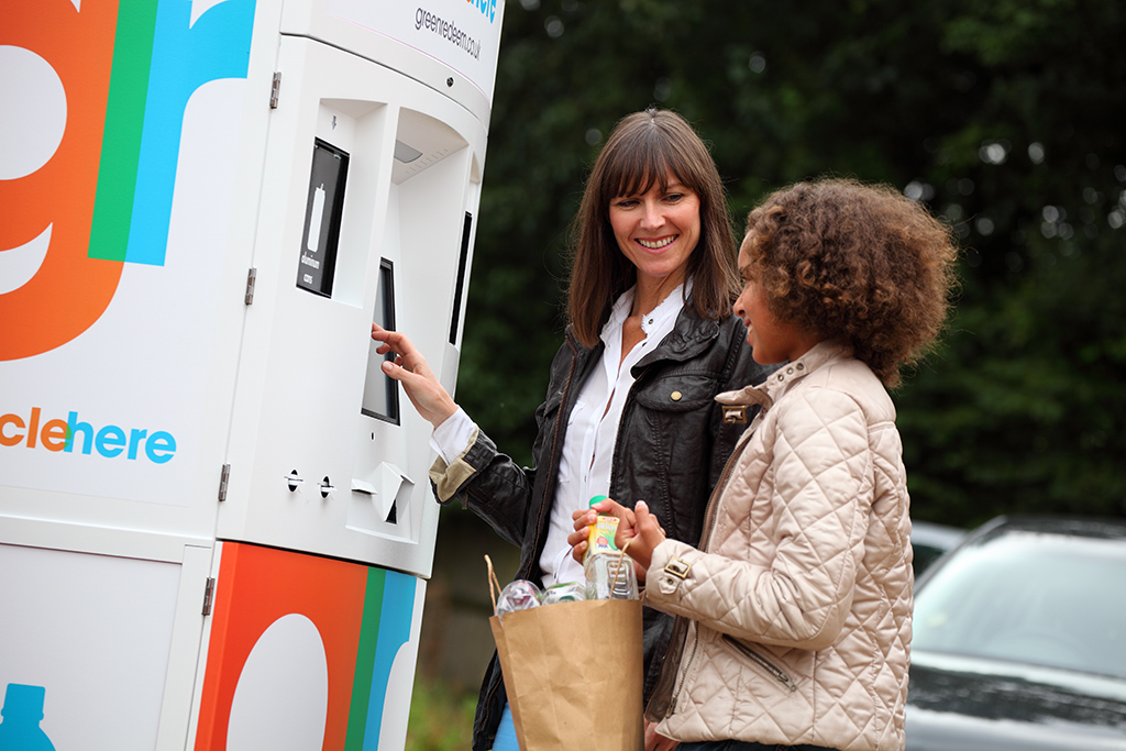 young girl and woman using the deposit return scheme kiosk with plastic bottles