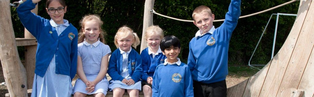 Primary school children standing on the climbing frame