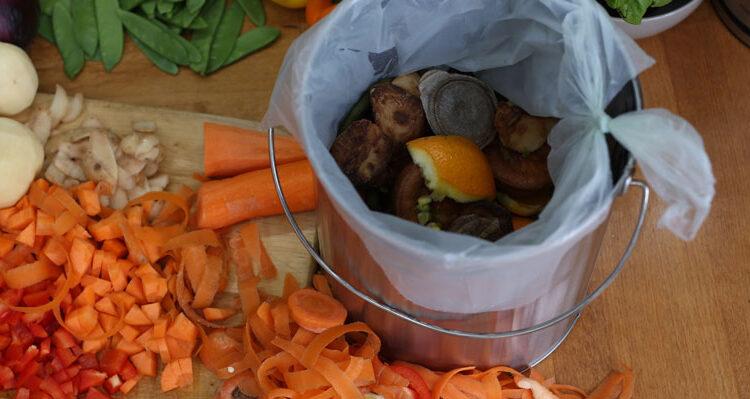 Food waste bin with peelings of vegetables on chopping board