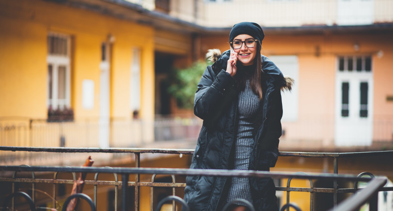 Woman standing on balcony with phone to her ear smiling