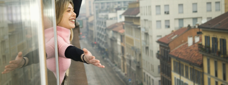 woman leaning out window to feel the breeze